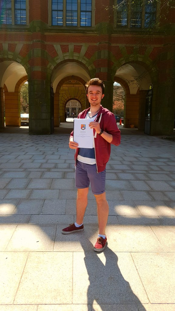 Josh Hamilton, holding his completed dissertation in front of the University of Birmingham clocktower, Old Joe.